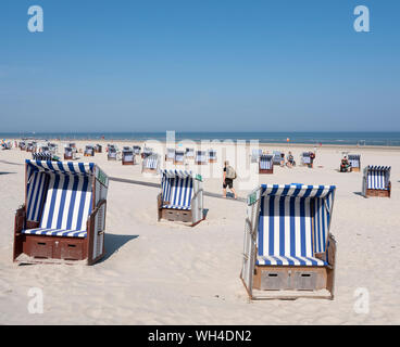man with rucksack passes beach korbs on the island of norderney in germany on sunny day - Stock Photo