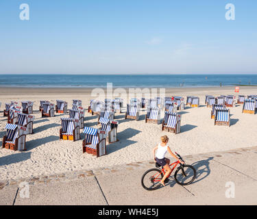 woman on bicycle passes beach korbs on the island of norderney in germany - Stock Photo