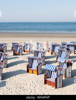 man in red shirt checks beach korbs on the island of norderney in germany on sunny day - Stock Photo