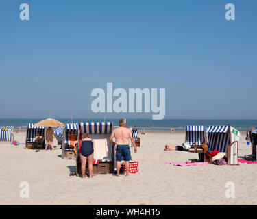 people in bathing suit use beach korbs on the island of norderney in germany - Stock Photo