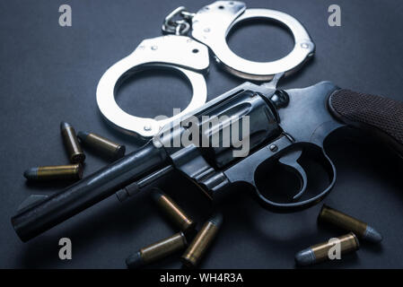 Gun with ammunition and shackle on black background - Stock Photo