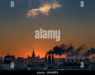 Smoke Emitting From Chimney At Factory Against Sky During Sunset - Stock Photo