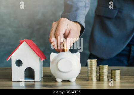 Midsection Of Businessman Inserting Coins In Piggy Bank - Stock Photo