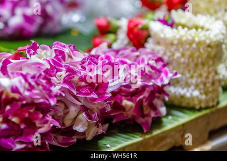 Various jasmine and orchide Phuang malai, traditional Thai flower garland offerings at Pak Khlong Talat, Bangkok flower market. Thailand. - Stock Photo