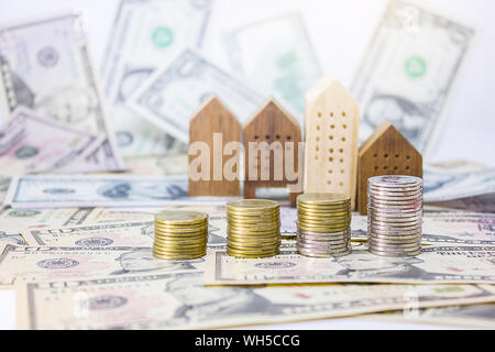 Stacked Coins With Model Houses And Paper Currencies