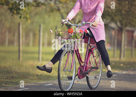 Low Section Of Woman Riding Bicycle On Road - Stock Photo