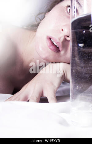Close-up Of Shirtless Woman Lying On Bed - Stock Photo