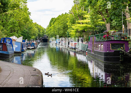 Colourful Narrow Boats Moored in Little Venice from Beneath the Warwick Avenue Road Bridge Over the Grand Union Canal With Watery Tree Reflections. - Stock Photo