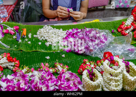 Woman making Phuang malai, traditional Thai flower garland offerings with jasmine and orchids at Pak Khlong Talat, Bangkok flower market. Thailand. - Stock Photo