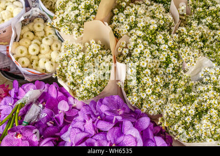 Bouquets of white aster flowers and purple orchids at Pak Khlong Talat, famous flower market in Bangkok, Thailand. - Stock Photo