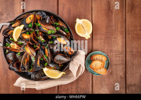 Marinara mussels, moules mariniere, with toasted bread and lemon slices, in a cooking pot, top shot on a dark rustic wooden background - Stock Photo