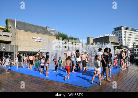 Children enjoying the water fountains outside Southbank Centre on a very hot Bank Holiday Monday, August 2019 UK - Stock Photo