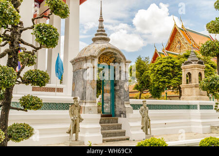Statues at the entrance of Wat Suthat Thepwararam, old royal Buddhist temple (wat) in Bangkok, Thailand. - Stock Photo