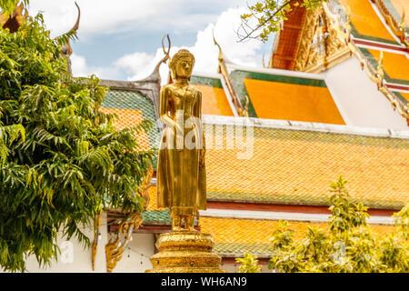 Golden statue at Wat Suthat Thepwararam, old royal Buddhist temple (wat) in Bangkok, Thailand. - Stock Photo