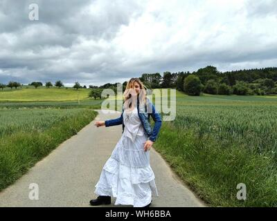 Happy Woman Dancing On Footpath Amidst Grassy Field Against Cloudy Sky - Stock Photo