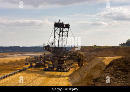 Giant bucket wheel excavator taking away the layers of ground before digging the brown coal. - Stock Photo