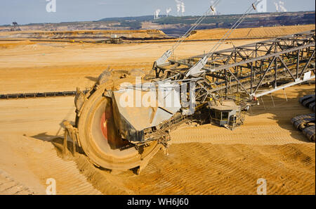 Giant bucket wheel excavator taking away the layers of ground before digging the brown coal. Largest open pit lignite mine in Europe. Power stations a - Stock Photo