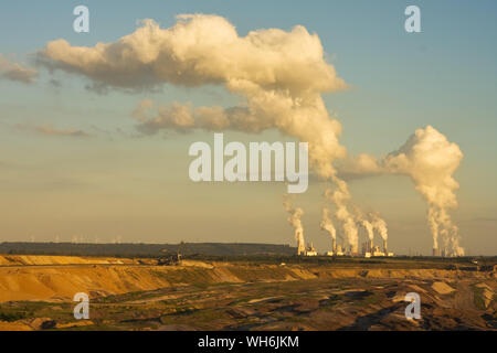 Open-pit mining for lignite (brown coal) that is burnt and tranformed to electricity by the power stations at the horizon - largest mining sites and p - Stock Photo