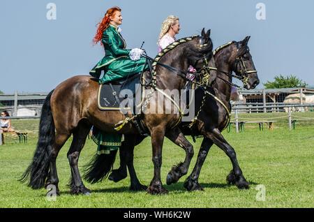 Schloss Hof Großes Pferdefest 2019 Great Equestrian Show at Schloss Hof Castle with two women riding on a side saddle - Stock Photo