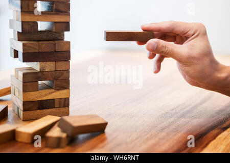 Cropped Hand Of Man Arranging Toy Blocks On Wooden Table - Stock Photo
