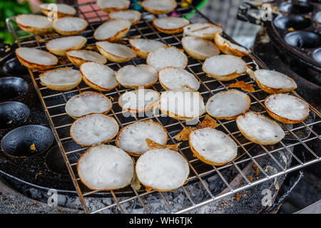 Khanom khrok or coconut-rice pancakes, Thai traditional dessert with coconut milk made on a special cast-iron pan. National cuisine of Thailand. - Stock Photo