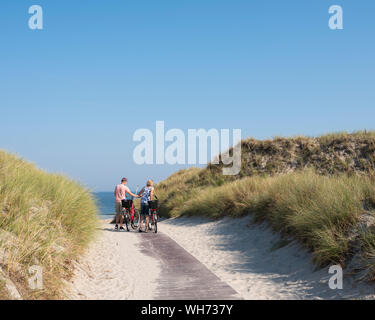 couple with bicycles at top of dunes near sea on german island of norderney on sunny summer day with blue sky - Stock Photo
