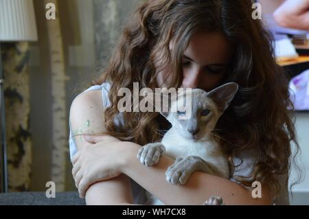 Close-up Of Young Woman Hugging Cat - Stock Photo