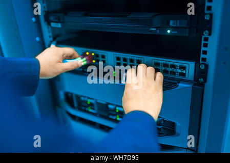 Cropped Hand Of Man Holding Computer Network Cables - Stock Photo