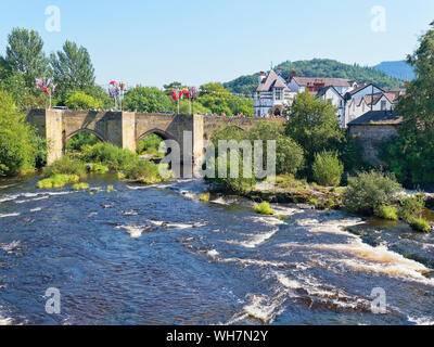 The fast flowing River Dee flows through the old stone bridge, draped in bunting and flags, in Llangollen, Wales - Stock Photo