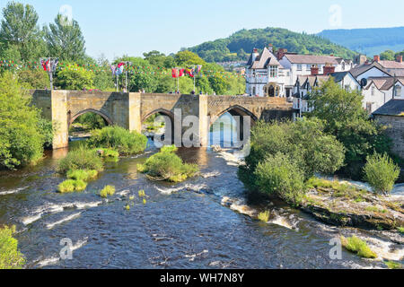 Hazy summer day in Llangollen, Wales. Flags flyalong the old stone bridge over the River Dee. - Stock Photo