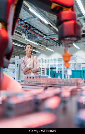 Businesswoman in a modern factory hall looking at robot - Stock Photo