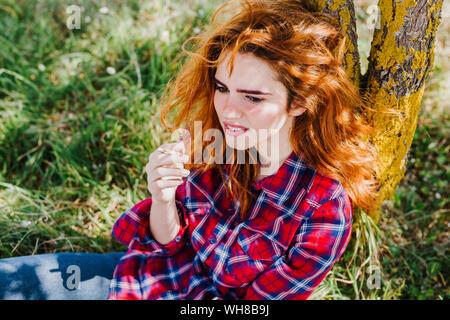 Portrait of redheaded woman having cigarette break under a tree