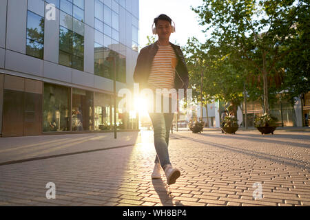 Portrait of smiling young man with headphones walking on street at backlight