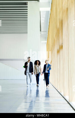 Young business people walking and talking in a hallway - Stock Photo