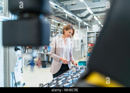 Businesswoman examining workpieces in a modern factory hall - Stock Photo