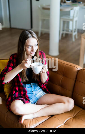 Relaxed young woman eating cereals in living room at home - Stock Photo