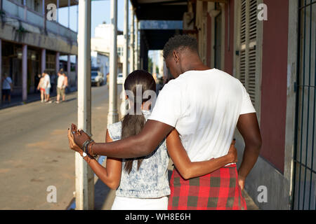 Young couple walking in the streets of Mabuto with arms around rear view