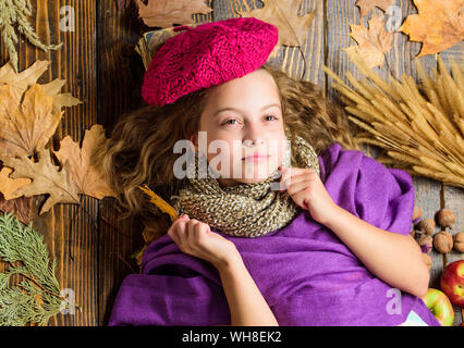 Autumn fashion hat accessory. Girl cute child in knitted hat lay wooden background fallen maple leaves top view. Fashion hat trend fall season. Kid girl bright soft knitted hat enjoy autumn. - Stock Photo
