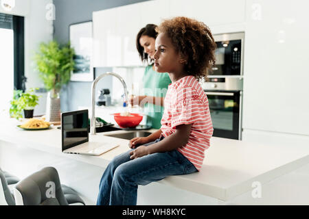 Girl sitting on kitchen counter with laptop and mother in background - Stock Photo