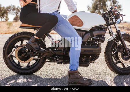 Couple sitting on motorbike, partial view - Stock Photo