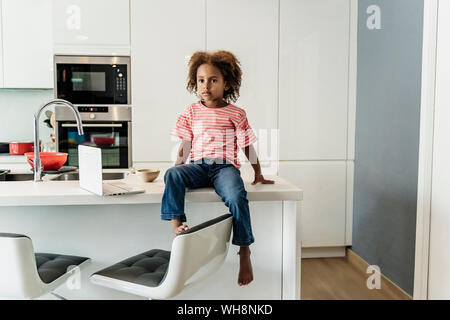 Girl with laptop sitting on kitchen counter - Stock Photo