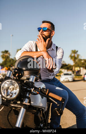 Portrait of bearded motorcyclist with mirrored sunglasses sitting on his motorbike smoking - Stock Photo