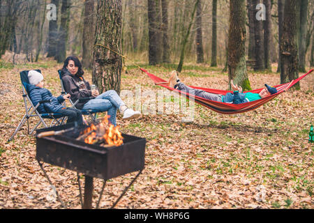 family resting at picnic. fire in grill. laying in hammock sitting in chairs. lifestyle - Stock Photo