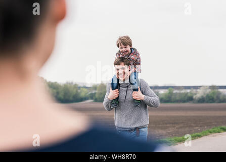 Happy family walking together next to fields, father carrying son piggyback