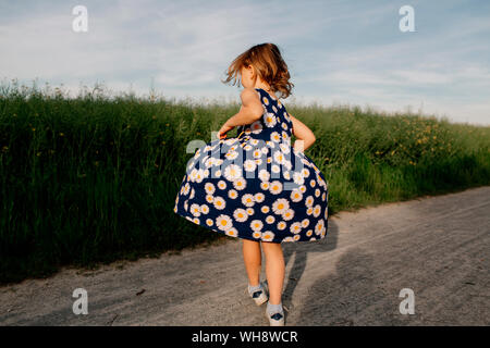 Back view of little girl wearing summer dress with floral design dancing on dirt track - Stock Photo