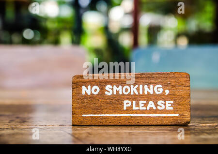 Close-up Of No Smoking Sign On Wooden Table - Stock Photo