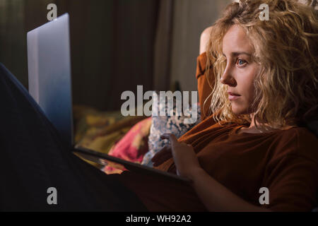 Portrait of blond young woman lying on bed using laptop - Stock Photo