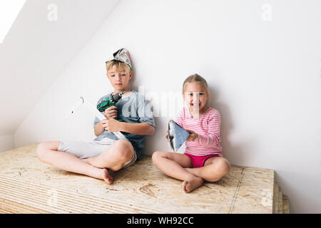Happy brother and sister in a home to be renovated - Stock Photo