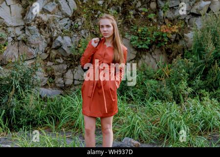 Portrait Of Young Woman Wearing Orange Dress On Grassy Field - Stock Photo