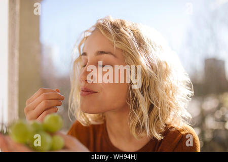 Portrait of blond young woman eating green grapes Stock Photo